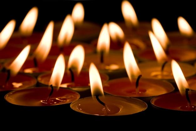 Gruppo di candele fiammeggianti sullo sfondo scuro
