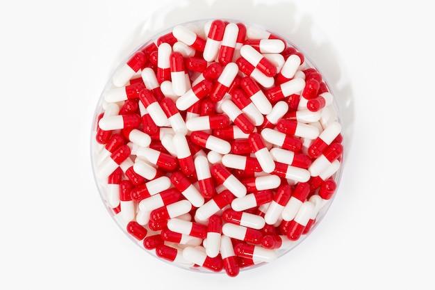 Gruppo di capsula della pillola in contenitore rotondo su fondo bianco. pillole bianche e rosse. concetto di medicina, assistenza sanitaria e farmacia