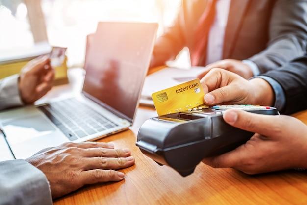 Gruppo di carta di credito della tenuta di affari con il sistema di pagamento di nfc in ufficio moderno.