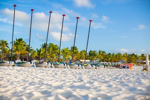 Gruppo di catamarani con vele colorate sulla spiaggia caraibica esotica