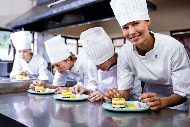 Gruppo di chef che guarniscono deliziosi dessert in un piatto