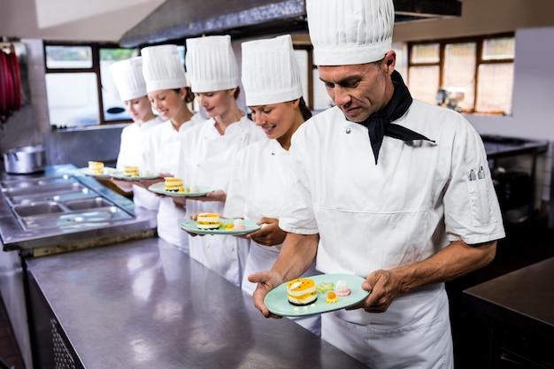 Gruppo di chef che tengono piatto di deliziosi dessert in cucina