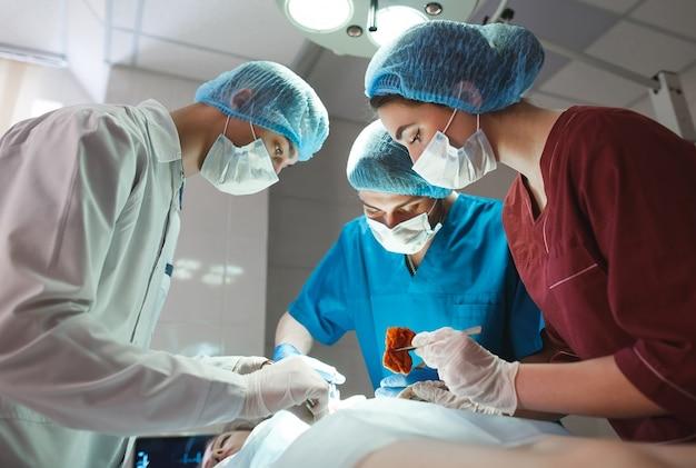 Gruppo di chirurghi al lavoro che operano in sala operatoria. squadra della medicina di rianimazione che indossa le maschere protettive che tengono gli strumenti medici d'acciaio che salvano paziente. chirurgia ed emergenza