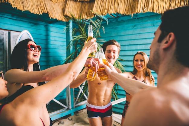 Gruppo di cinque amici che festeggiano nella loro casa al mare estiva