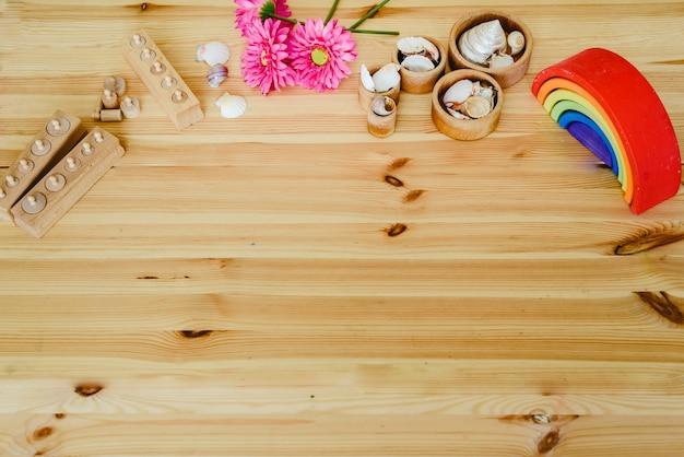 Gruppo di ciotole di legno rotondi pieni di conchiglie e fiori viola