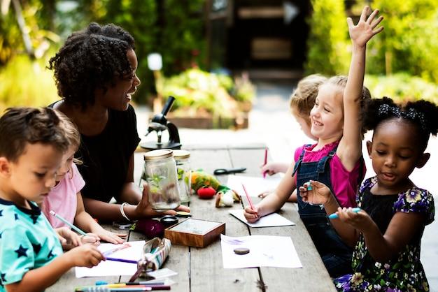 Gruppo di compagni di classe per bambini che imparano lezione di disegno di biologia