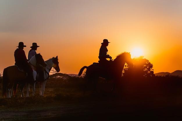 Gruppo di cowboy a cavallo.