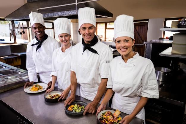 Gruppo di cuochi unici che tengono piatto di alimento pronto in cucina