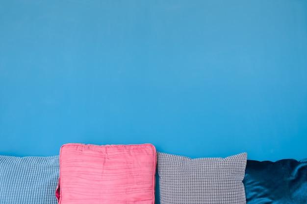 Gruppo di cuscini sul fondo blu vibrante della parete con lo spazio della copia per progettazione