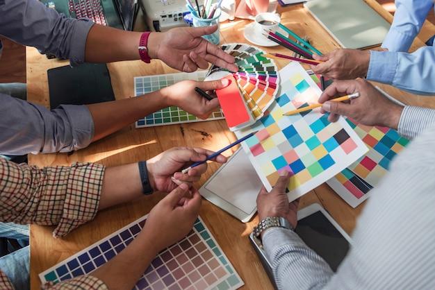 Gruppo di designer asiatici di brainstorming che lavorano insieme a colleghi e campioni di colore