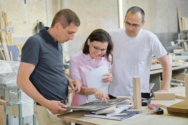Gruppo di designer, clienti, falegnami, ingegneri che scelgono prodotti in legno