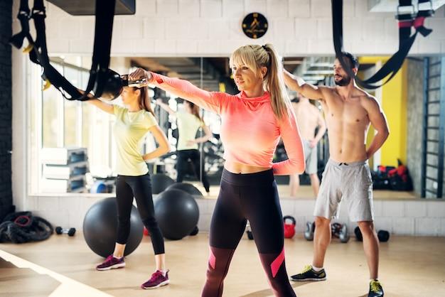 Gruppo di determinati atleti concentrati che fanno esercizi con la campana del bollitore per braccia e schiena.
