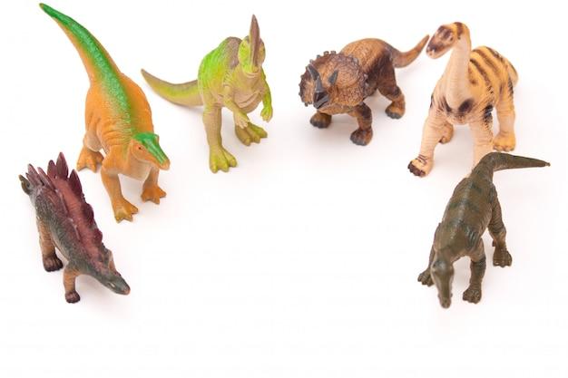 Gruppo di dinosauri di plastica del giocattolo sui precedenti bianchi.