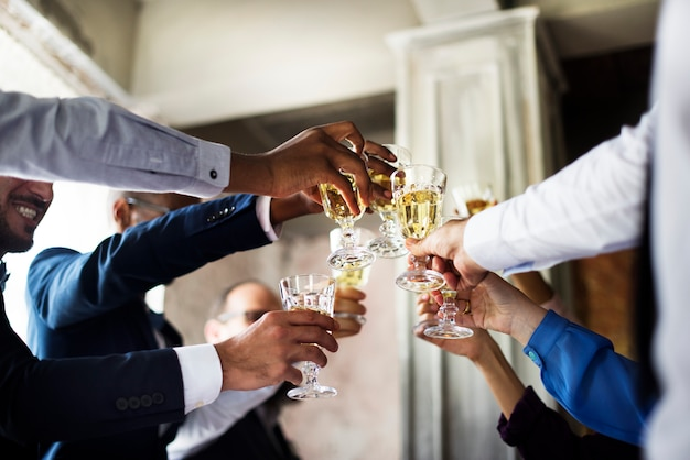 Gruppo di diversa gente che tintinnano i vetri di vino insieme celebrazione di congratulazioni
