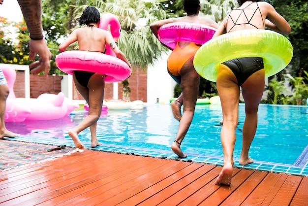 Gruppo di diverse donne che saltano allo stagno con tubo gonfiabile che gode dell'ora legale