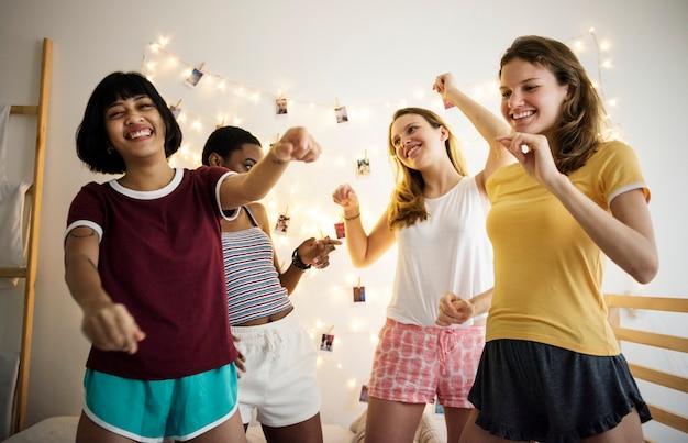 Gruppo di diverse donne divertirsi insieme sul letto