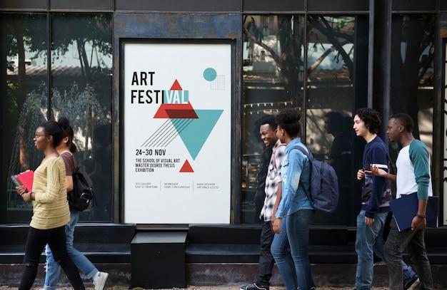 Gruppo di diversi amici che camminano passano cartellone di mostra d'arte
