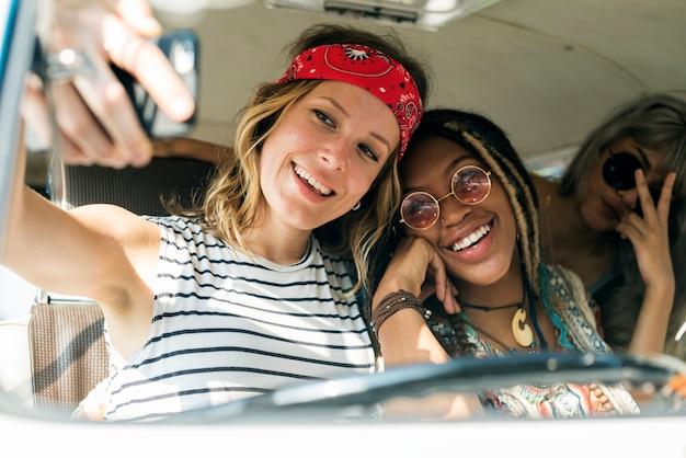 Gruppo di diversi amici sul viaggio stradale che prende insieme selfie