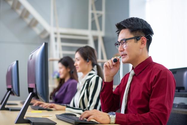 Gruppo di diverso gruppo di telemarketing nel fondo dell'insegna dell'ufficio della call center