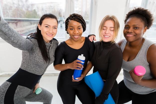 Gruppo di donne a lezione di fitness prendendo autoscatti