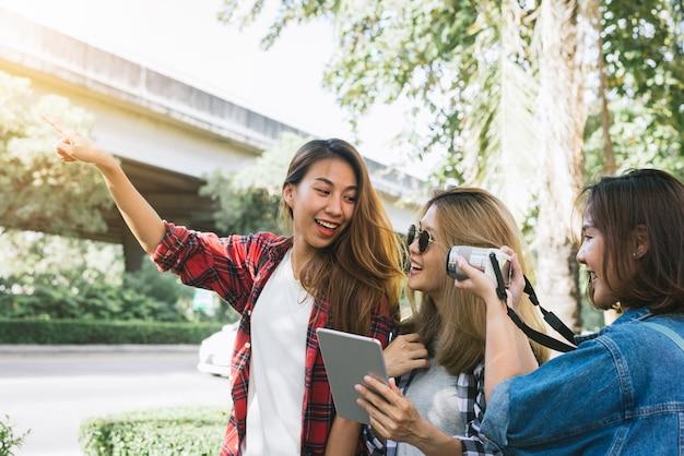 Gruppo di donne asiatiche che utilizzano la macchina fotografica per fare foto mentre si viaggia al parco in città urbana a bangkok