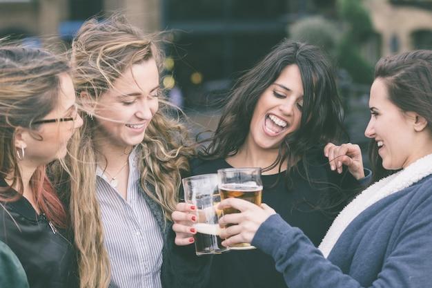 Gruppo di donne che godono di una birra al pub a londra.