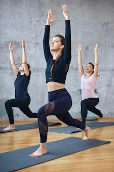 Gruppo di donne che praticano stretching su stuoie.