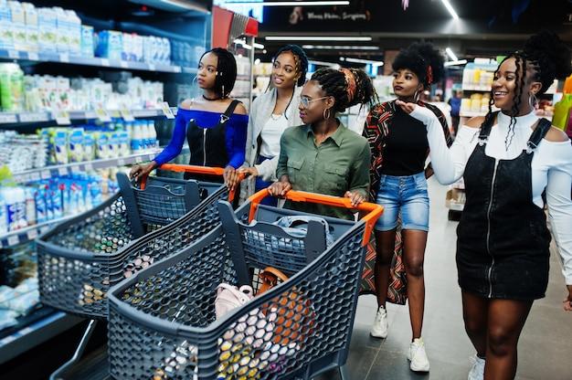 Gruppo di donne con i carrelli vicino allo scaffale del frigorifero che vende i prodotti lattiero-caseari fatti da latte nel supermercato