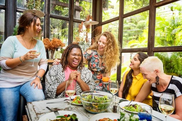 Gruppo di donne di diversità che appende mangiando concetto insieme