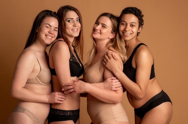 Gruppo di donne felici diverse in biancheria intima su sfondo grigio