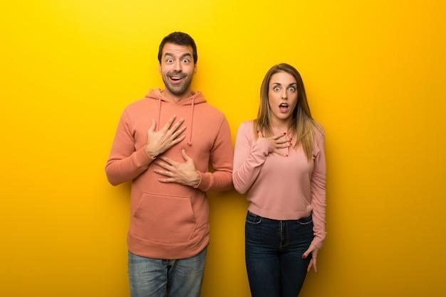 Gruppo di due persone su sfondo giallo sorpreso e scioccato mentre guardando a destra