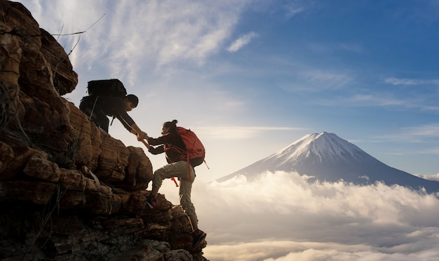 Gruppo di escursioni in asia si aiutano a vicenda silhouette in montagna con la luce del sole.