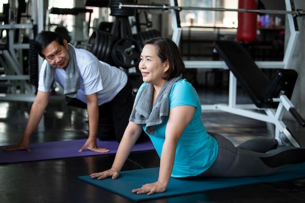 Gruppo di esercizio d'allungamento senior asiatico dell'amico alla palestra di yoga. stile di vita sano degli anziani.