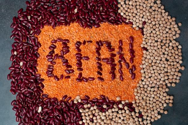 Gruppo di fagioli, lenticchie e ceci su sfondo nero. assortimento di fagioli. cartello