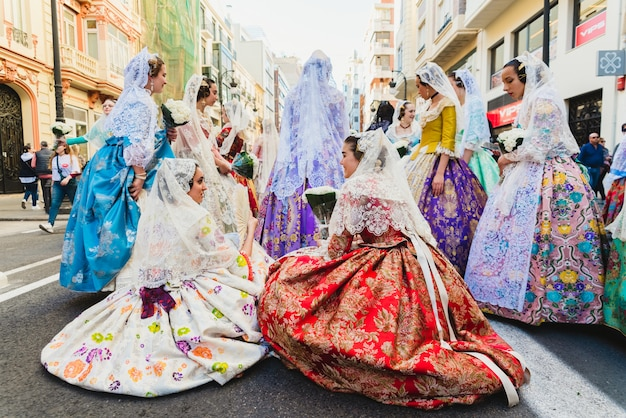 Gruppo di falleras e falleros che riposano nelle strade mentre aspettano il loro turno per sfilare con il loro tipico costume spagnolo.