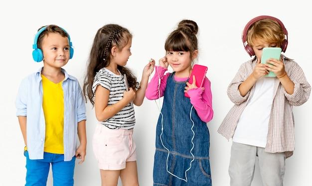 Gruppo di felicità di bambini adorabili e adorabili che ascoltano musica