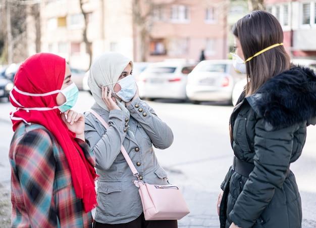 Gruppo di femmine sulla strada con maschere contro l'inquinamento