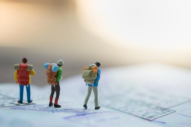 Gruppo di figure in miniatura del viaggiatore con lo zaino che cammina sul passaporto con i bolli di immigrazione.