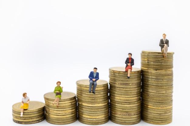 Gruppo di figure miniatura della donna e dell'uomo d'affari che si siedono sopra la pila di monete di oro su bianco.
