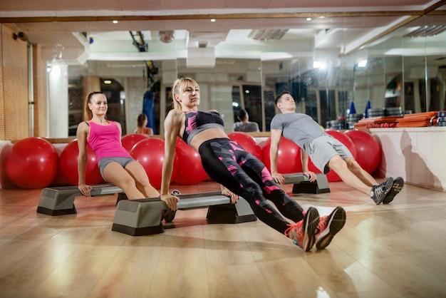 Gruppo di forma fisica sportiva attiva di forma sana attraente che fa posa ascendente della plancia di purvottanasana sugli stepper in palestra.
