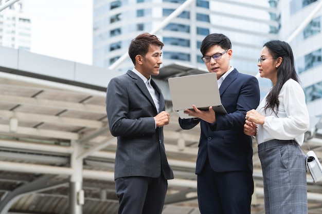 Gruppo di gente di affari asiatica che lavora e che discute qualcosa di positivo con il suo collega maturo e che utilizza un computer portatile ad all'aperto nella capitale