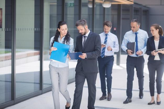 Gruppo di gente di affari che cammina fuori dell'edificio per uffici