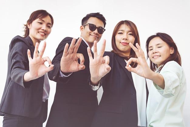 Gruppo di gente di affari felice che mostra gesto giusto
