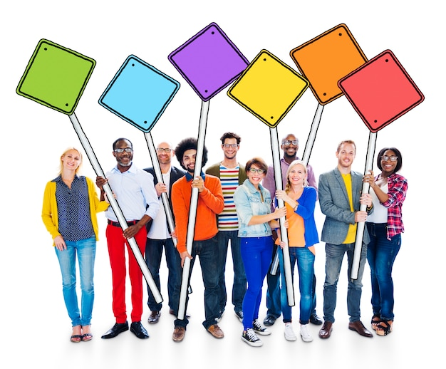 Gruppo di gente multi-etnica felice che tiene concetto dei pali del segno