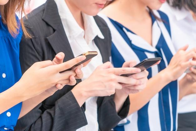 Gruppo di giovane donna che utilizza il telefono cellulare digitale della compressa