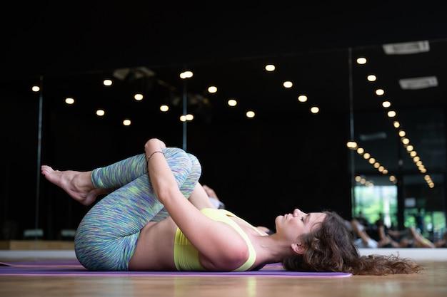 Gruppo di giovane donna sportiva, persone attraenti che praticano la lezione di yoga in palestra