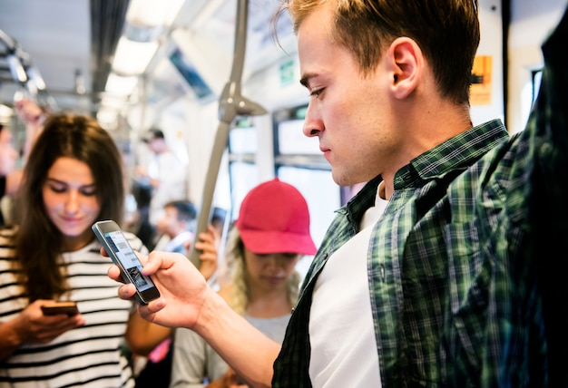 Gruppo di giovani amici adulti che utilizzano gli smartphone nella metropolitana