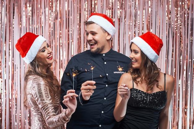 Gruppo di giovani amici che godono della celebrazione del nuovo anno con le scintille nelle mani.