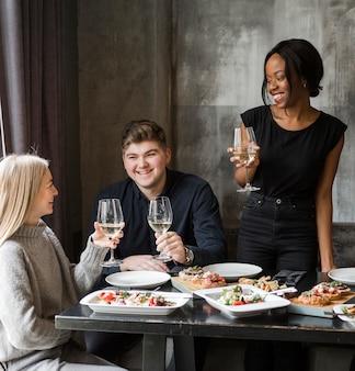 Gruppo di giovani amici che mangiano vino insieme