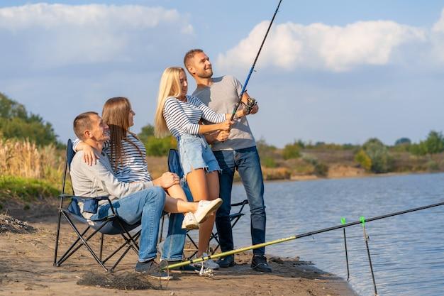 Gruppo di giovani amici che pescano sul molo sul lago